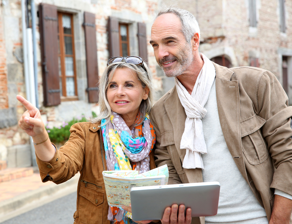 Senior couple visiting city with map and tablet